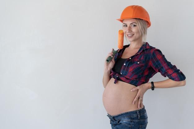 Jeune femme blonde avec un sourire sur son visage regarde le photographe .. fille enceinte. tenez le rouleau à peinture. espace de copie.