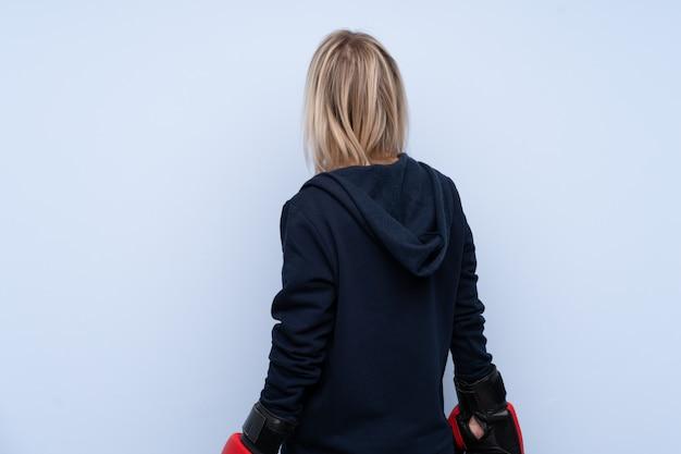 Jeune femme blonde sport sur mur bleu isolé avec des gants de boxe