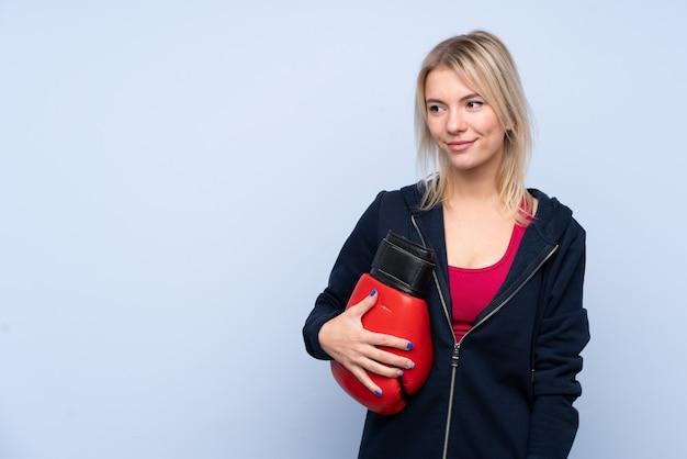 Jeune femme blonde sport sur wallwith bleu isolé avec des gants de boxe