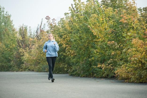 Jeune femme blonde sportive et en bonne santé en vêtements de sport jogging sur la route dans le parc parmi les arbres verts et jaunes le matin en automne