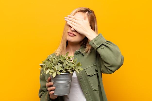 Jeune femme blonde à stressé, honteux ou contrarié, avec un mal de tête, couvrant le visage avec la main