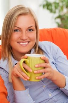 Jeune femme blonde avec une tasse