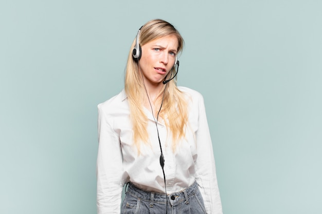 Jeune femme blonde de télévendeur se sentant perplexe et confuse, avec une expression stupide et abasourdie en regardant quelque chose d'inattendu