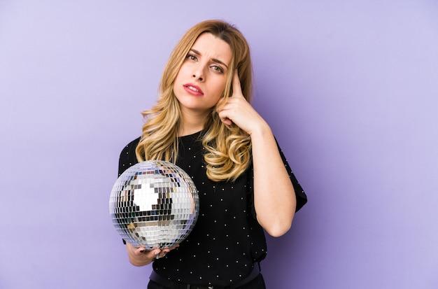Jeune femme blonde tenant un ballon de fête de nuit isolé montrant un geste de déception avec l'index.