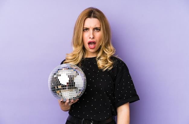 Jeune femme blonde tenant une boule de fête de nuit isolée crier très en colère et agressif.
