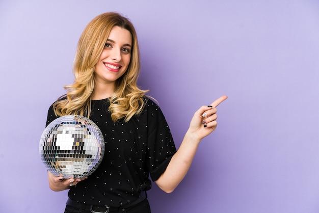Jeune femme blonde tenant une boule de fête de nuit isolée souriant et pointant de côté, montrant quelque chose à l'espace vide.
