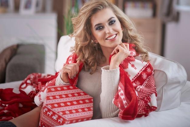Jeune femme blonde tenant un cadeau de noël