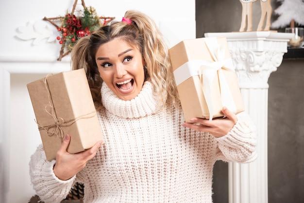Jeune femme blonde tenant des cadeaux heureusement près de la cheminée.
