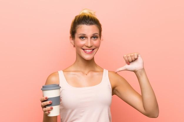 Jeune femme blonde tenant un café à emporter fière et satisfaite