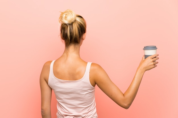 Jeune femme blonde tenant un café à emporter en position arrière