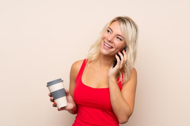 Jeune femme blonde tenant un café à emporter et un téléphone portable