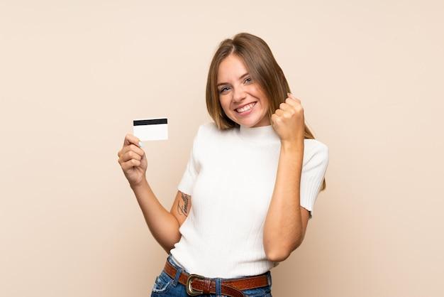 Jeune femme blonde tenant une carte de crédit