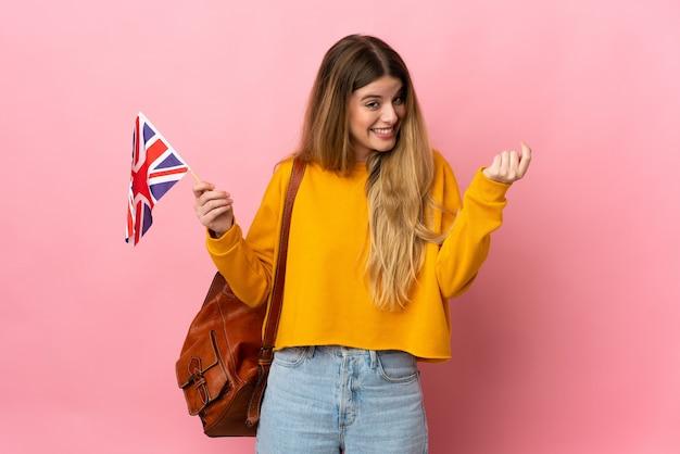 Jeune femme blonde tenant un drapeau du royaume-uni isolé sur un mur blanc faisant un geste d'argent