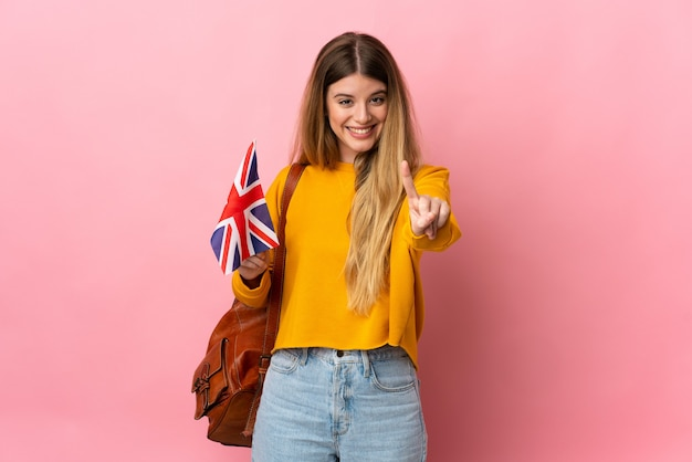 Jeune femme blonde tenant un drapeau du royaume-uni isolé sur un mur blanc montrant et en soulevant un doigt