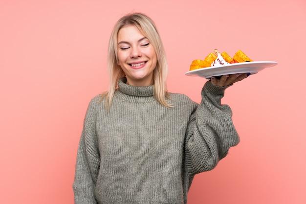Jeune femme blonde tenant des gaufres sur un mur rose isolé avec une expression heureuse