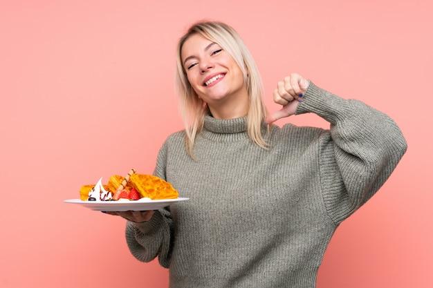 Jeune femme blonde tenant des gaufres sur un mur rose isolé, fier et satisfait de lui-même