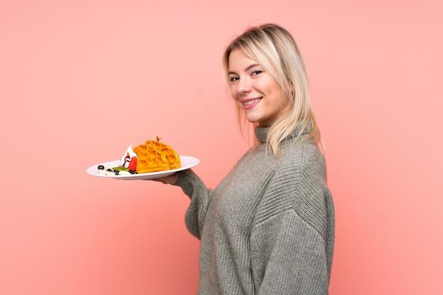 Jeune femme blonde tenant des gaufres sur un mur rose isolé, souriant beaucoup