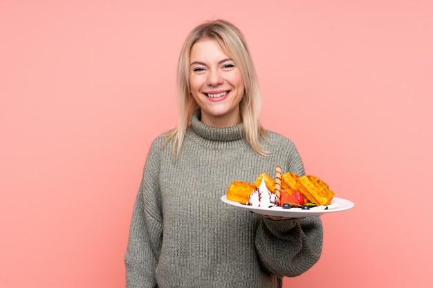 Jeune femme blonde tenant des gaufres souriant beaucoup