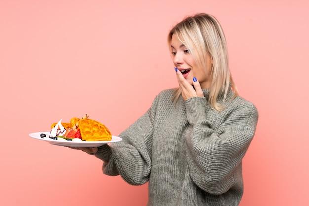 Jeune femme blonde tenant des gaufres avec surprise et expression faciale choquée