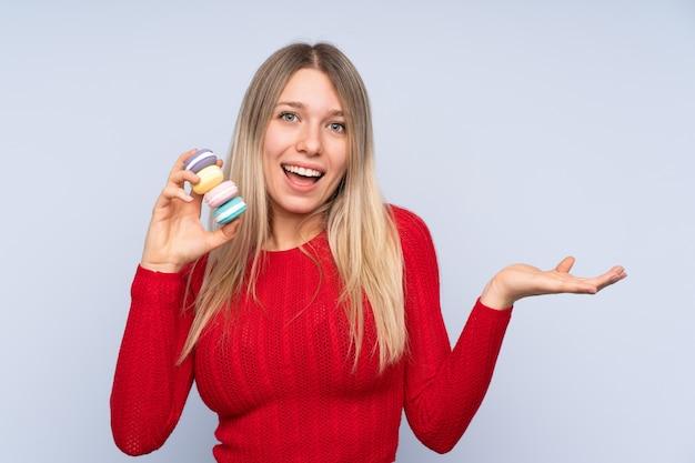 Jeune femme blonde tenant des macarons français colorés avec une expression choquée