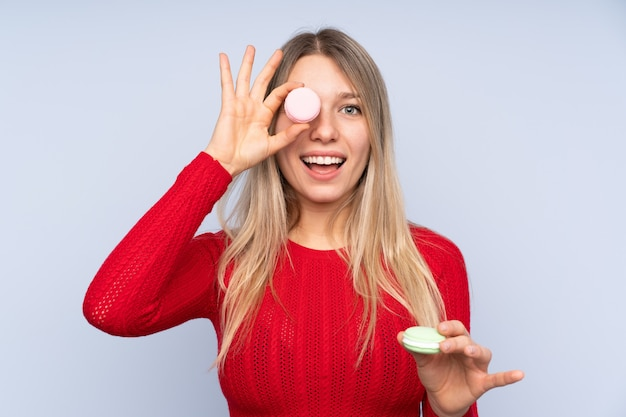 Jeune femme blonde tenant des macarons français colorés