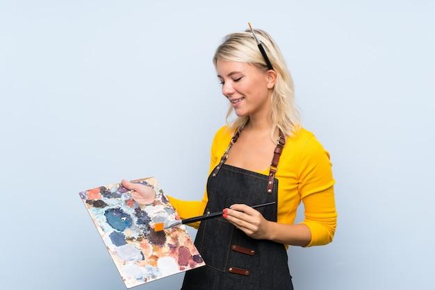 Jeune femme blonde tenant une palette