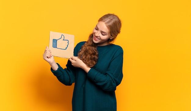 Jeune femme blonde tenant une pancarte avec comme symbole
