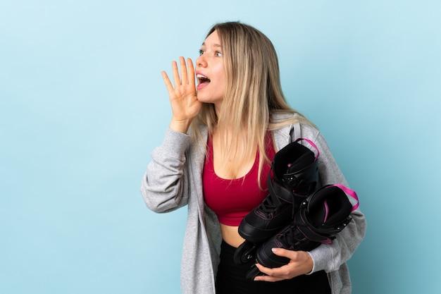 Jeune femme blonde tenant un patins à roulettes isolé sur mur rose criant avec la bouche grande ouverte
