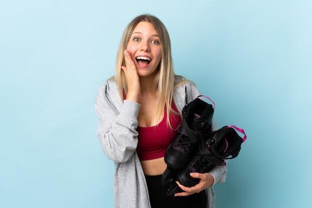 Jeune femme blonde tenant un patins à roulettes isolé sur mur rose avec une expression faciale surprise