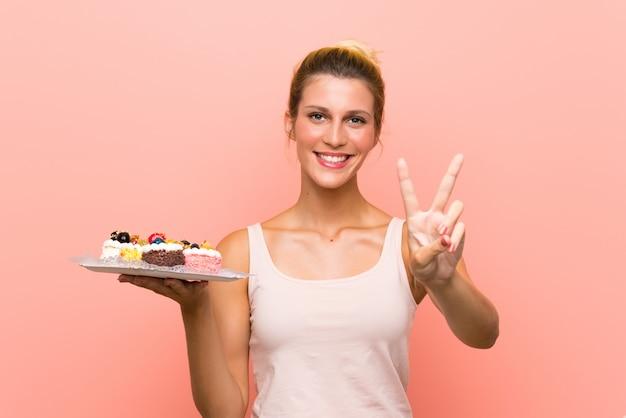 Jeune femme blonde tenant plein de mini gâteaux différents souriant et montrant le signe de la victoire