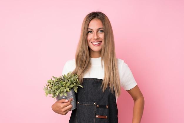 Jeune femme blonde tenant un pot de fleurs