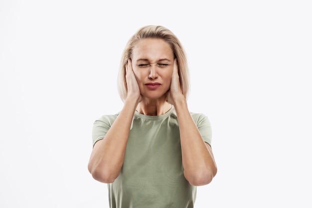 Jeune femme blonde tenant sa tête. maux de tête, problèmes et stress.