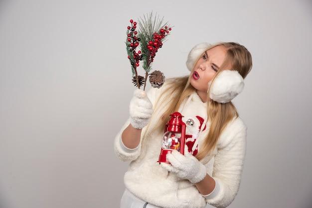 Jeune femme blonde en tenue blanche regardant les baies de houx.