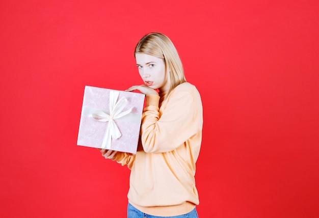 Jeune femme blonde tient la boîte-cadeau tout en s'inquiétant devant le mur rouge