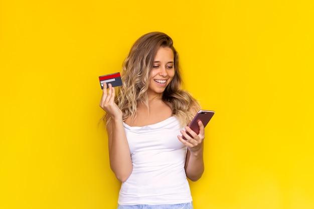 Une jeune femme blonde tient une carte de crédit en plastique dans sa main en regardant l'écran du téléphone portable