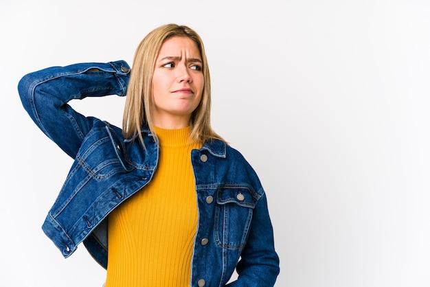 Jeune femme blonde touchant l'arrière de la tête, pensant et faisant un choix