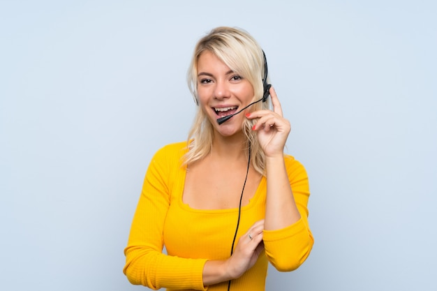 Jeune femme blonde travaillant avec un casque