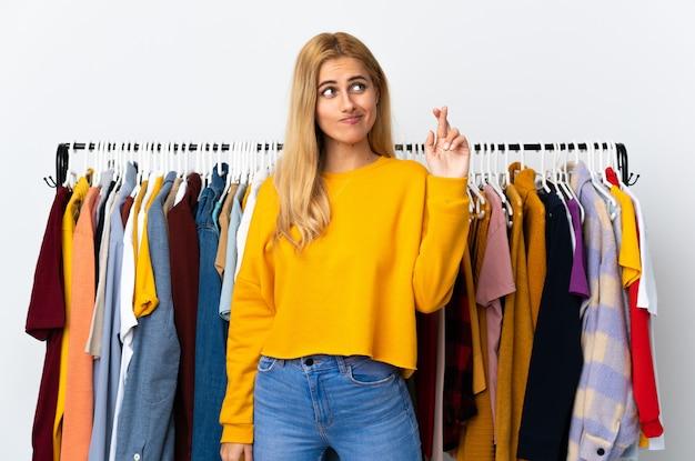 Jeune femme blonde uruguayenne dans un magasin de vêtements avec les doigts se croisant et souhaitant le meilleur