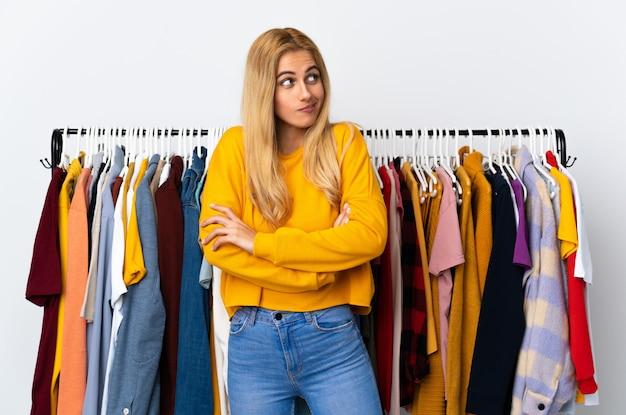 Jeune femme blonde uruguayenne dans un magasin de vêtements faisant des gestes de doutes tout en soulevant les épaules