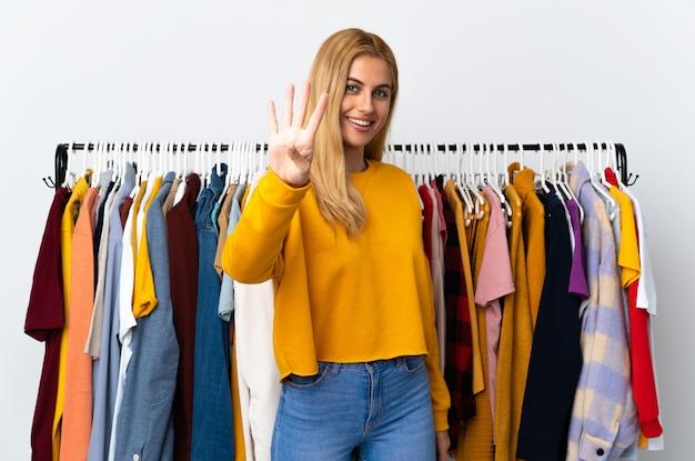 Jeune femme blonde uruguayenne dans un magasin de vêtements heureux et en comptant quatre avec les doigts