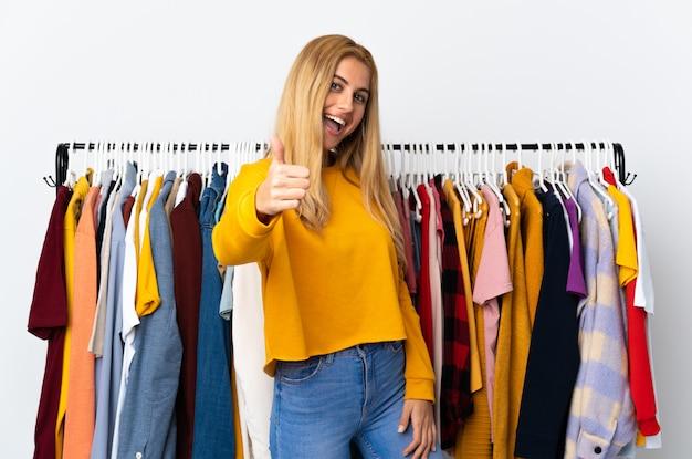 Jeune femme blonde uruguayenne dans un magasin de vêtements avec les pouces vers le haut parce que quelque chose de bien s'est produit