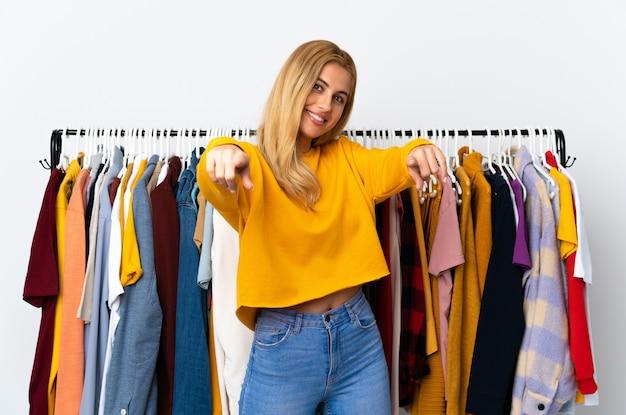 Jeune femme blonde uruguayenne dans un magasin de vêtements vous montre du doigt en souriant