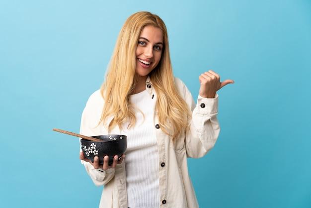 Jeune femme blonde uruguayenne sur mur bleu isolé pointant vers le côté pour présenter un produit tout en tenant un bol de nouilles avec des baguettes