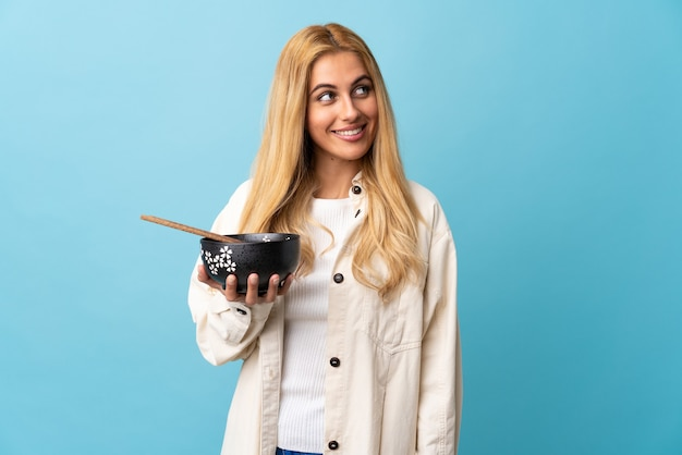 Jeune femme blonde uruguayenne sur mur bleu isolé regardant tout en souriant tout en tenant un bol de nouilles avec des baguettes