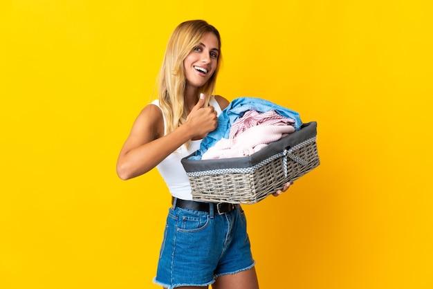 Jeune femme blonde uruguayenne tenant un panier de vêtements isolé sur jaune donnant un geste de pouce en l'air