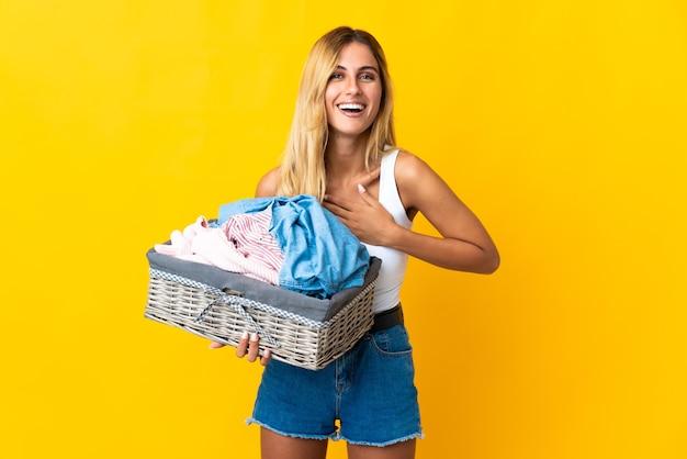 Jeune femme blonde uruguayenne tenant un panier de vêtements isolé sur jaune souriant beaucoup