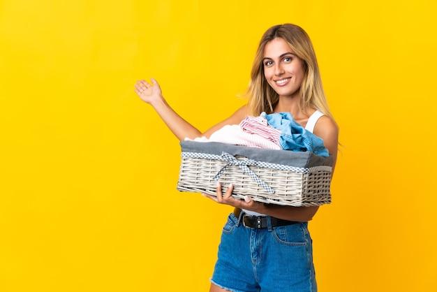 Jeune femme blonde uruguayenne tenant un panier de vêtements isolé sur mur jaune étendant les mains sur le côté pour inviter à venir