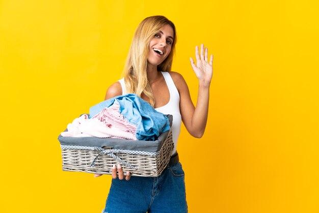 Jeune femme blonde uruguayenne tenant un panier de vêtements isolé sur mur jaune saluant avec la main avec une expression heureuse