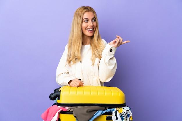 Jeune femme blonde uruguayenne avec une valise pleine de vêtements sur un mur violet isolé dans l'intention de réaliser la solution tout en levant un doigt