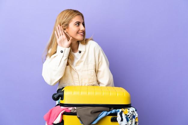 Jeune femme blonde uruguayenne avec une valise pleine de vêtements sur un mur violet isolé écouter quelque chose en mettant la main sur l'oreille